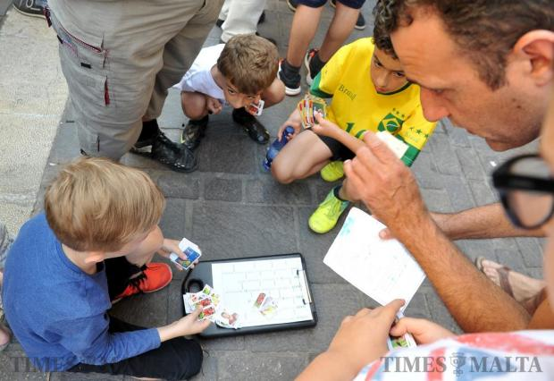 Children and adults alike meet outside Anastasi's in Valletta on June 4, to exchange football stickers in the hope of completing the Panini album for the 2016 European Cup. Photo: Chris Sant Fournier