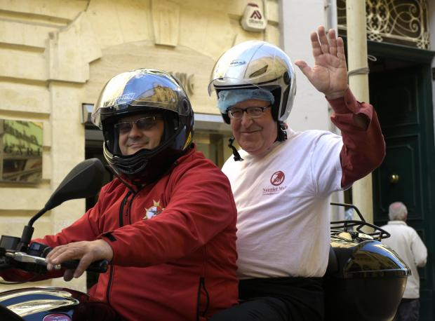 A grandfather waves to the camera whilst riding on motorcycle in Valletta celebrating Jum in-nanniet on March 12. Photo: Mark Zammit Cordina