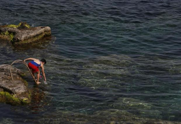 A woman tests the sea water temperature before going for a swim at Ghar Lapsi, outside Siggiewi, on April 13. Photo: Darrin Zammit Lupi