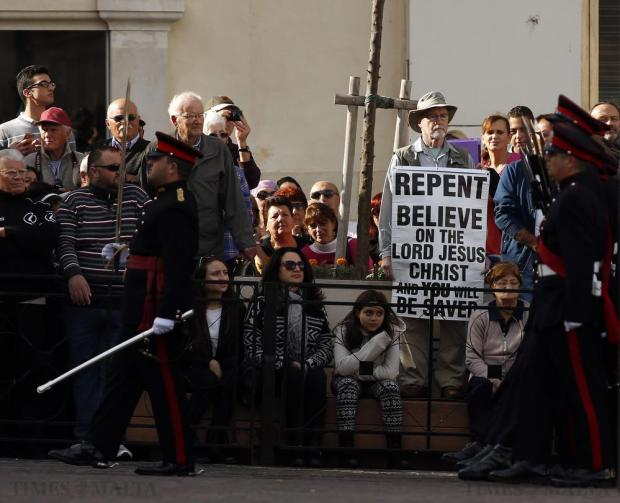 A man holding a poster calling on people to repent attends an Armed Forces of Malta military parade marking Malta's Republic Day in Valletta on December 13. Malta, a former British colony, became a republic in 1974, 10 years after gaining independence. Photo: Darrin Zammit Lupi