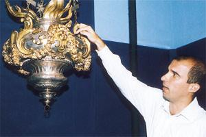 Baroque historian Keith Sciberras pointing out a detail of an oil lamp designed by Melchiorre Cafà. The lamp is one of the exhibits at the Museum of Fine Arts. Picture: Chris Sant Fournier courtesy of the owners and Heritage Malta.