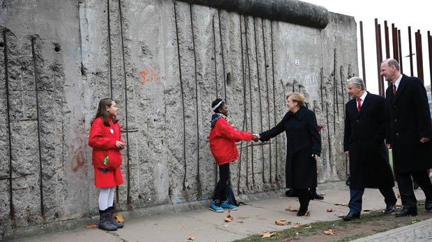 German Chancellor Angela Merkel, Berlin Mayor Klaus Wowereit and Director of the Berlin Wall Foundation Axel Klausmeier (right) shake hands with children symbolising the so-called Mauerspechte ('wall peckers', people who chipped the wall with hammers) during a ceremony marking the 25th anniversary of the fall of the Berlin Wall at a memorial in Bernauer Strasse, in Berlin, yesterday. Photo: Reuters