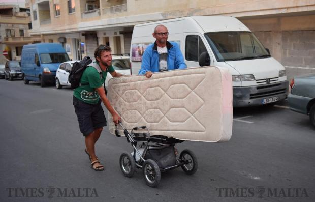 Two men move a mattress onto a pram in the roads of St Paul's Bay on May 17 . Photo: Mark Zammit Cordina