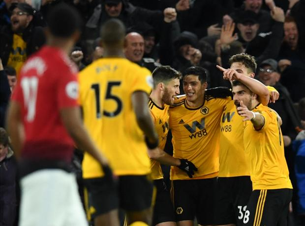 Wolves players celebrate a goal against Manchester United.