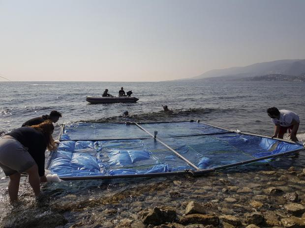 Greek university students gently deposits a wall-sized PVC frame on the surface before divers moor them at sea at a beach in the island of Lesbos on April 18, 2019. Holding in plastic bags and bottles, the four 5-by-5-metre frames are part of an experiment to determine if seaborne litter can be detected with EU satellites and drones.