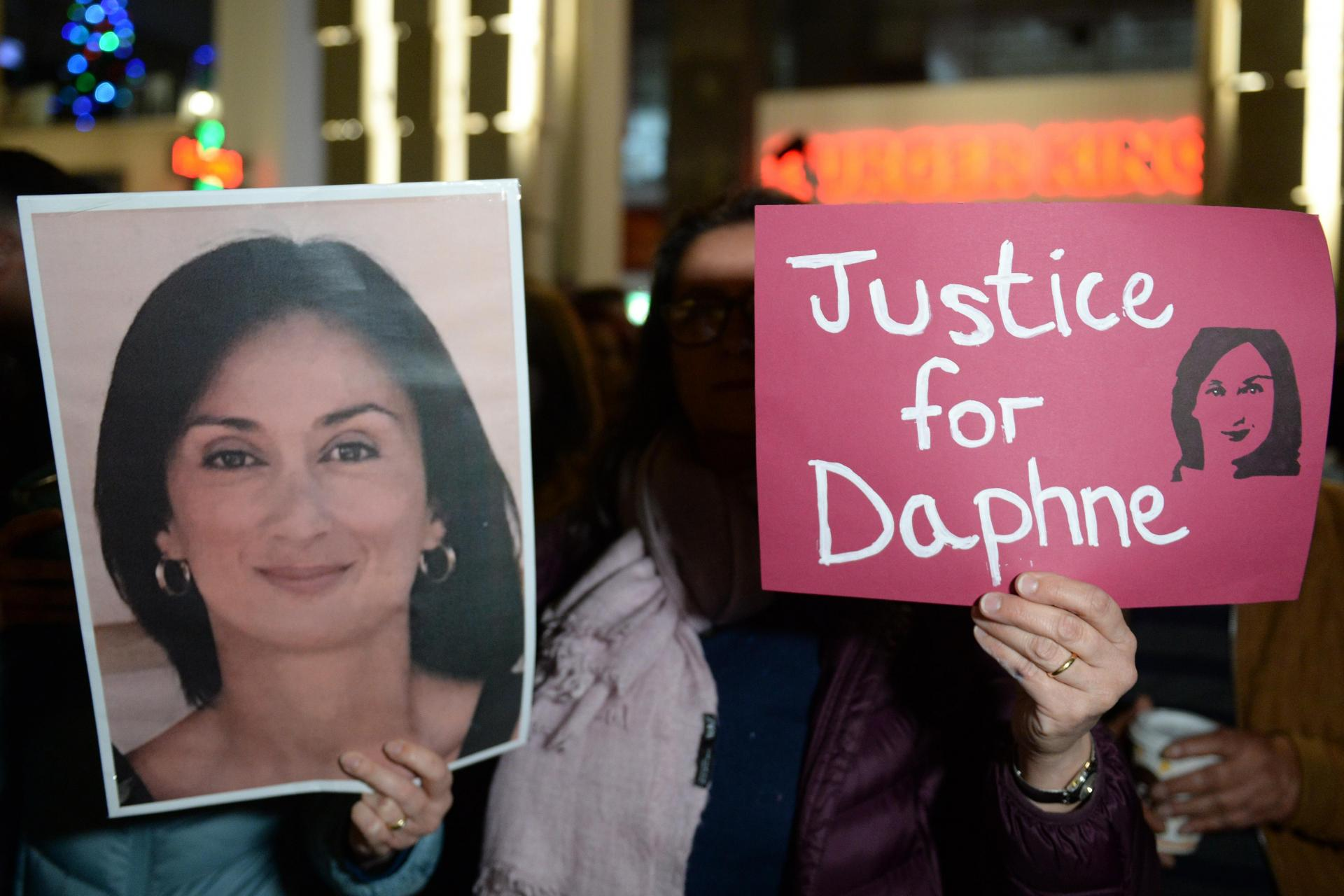 Activists hold up a placard and a portrait of murder journalist Daphne Caruana Galizia during a demonstration last week. Photo: Matthew Mirabelli