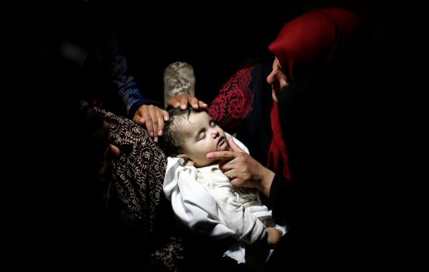 A relative mourns as she carries the body of eight-month-old Palestinian infant Laila al-Ghandour, who died after inhaling tear gas during Monday's protests. Photo: Reuters