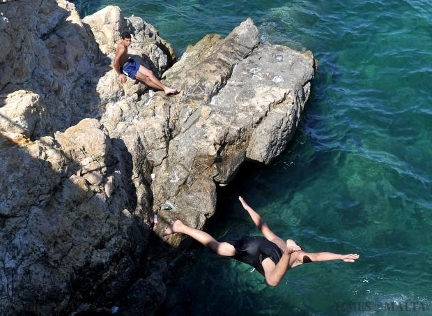 A man dives into the sea from the Sliema promenade on August 10. Photo: Chris Sant Fournier