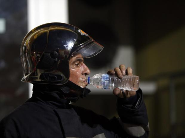 A Civil Protection fire-fighter drinks water after helping bring a fire at Dailies Food Store under control in Zebbug on July 9. Photo: Darrin Zammit Lupi