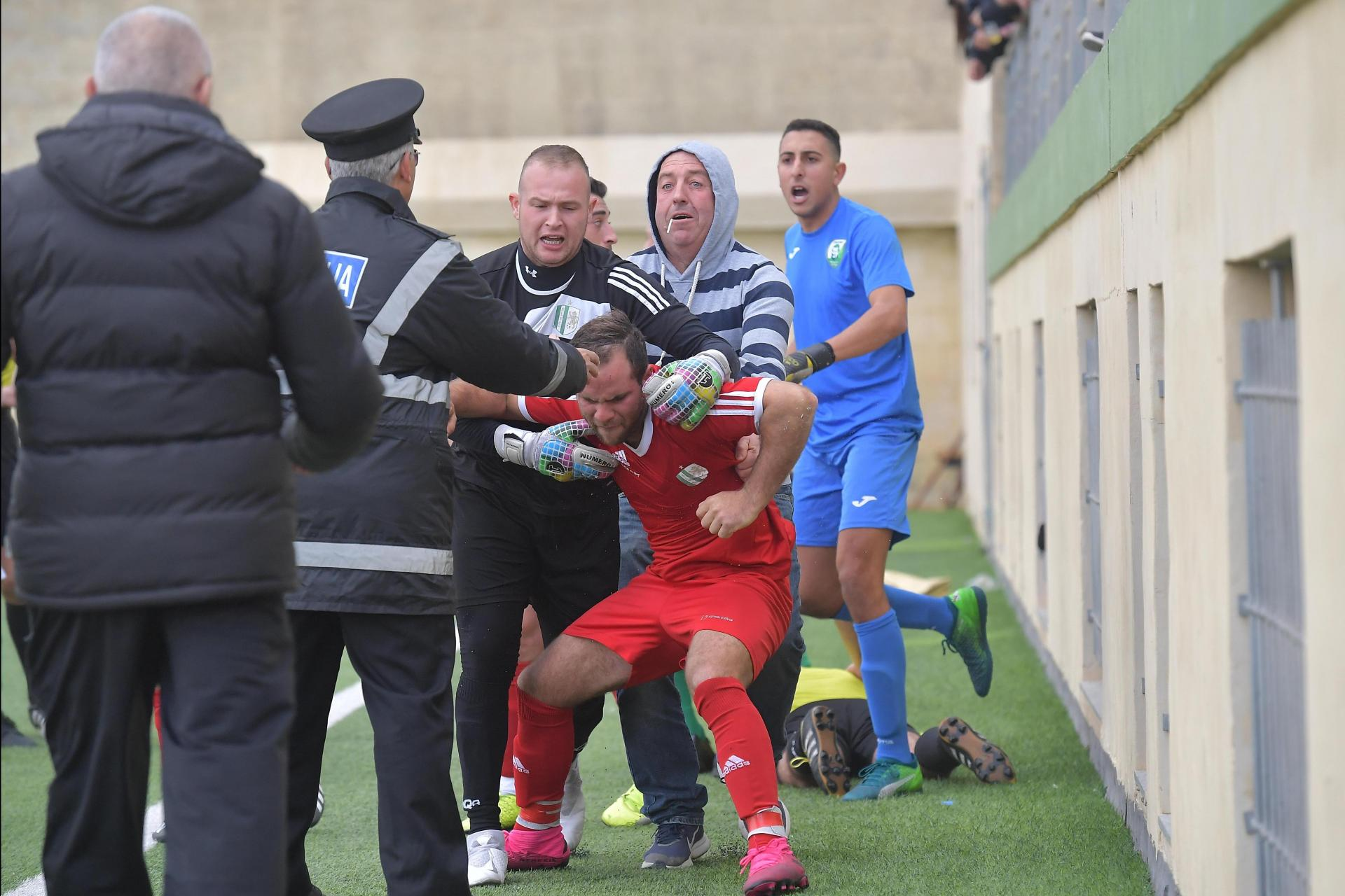 Antoine Camilleri is restrained by his team-mates after he was sent off against Oratory Youths.