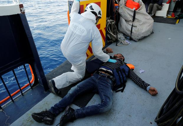 A crewman of the Malta-based NGO Migrant Offshore Aid Station (MOAS) ship Phoenix tends to an unconscious migrant. Photo - Darrin Zammit Lupi (Reuters).