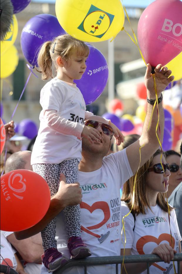 A girl holds on to a balloon in St George's Square after completing the President's Fun Run on November 19. Photo: Matthew Mirabelli