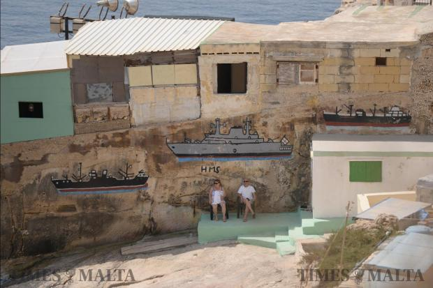 Tourists enjoy the beautiful weather in the shadow of vintage graffiti, in an area known as Taħt iż-Żiemel, beneath the Mediterranean Conference Centre in Valletta on June 1. Photo: Matthew Mirabelli