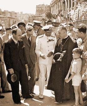 King George VI at Senglea Terrace speaking to Archpriest of Senglea Canon Emmanuel Brincat, surrounded by people.