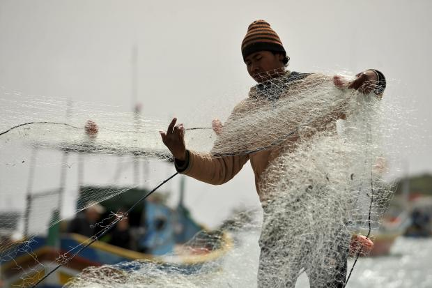 A fisherman prepares a fishing net at Marsaxlokk on March 7. Photo: Chris Sant Fournier