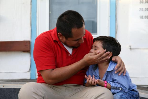 Walter Armando Jimenez Melendez, an asylum seeker from El Salvador, arrives with his four year-old son Jeremy at La Posada Providencia shelter in San Benito, Texas, US, shortly after he said they were reunited following separation since late May.