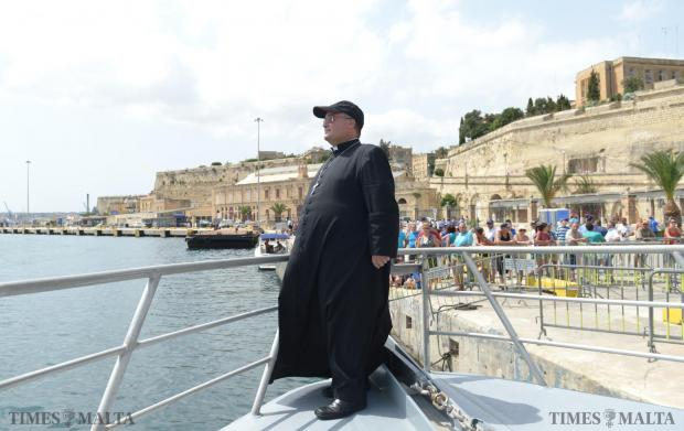 Standing At the helm, Archbishop Charles Scicluna waits for the start of the first race of the regatta in the Grand Harbour on September 8. Photo: Matthew Mirabelli