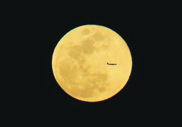 A passenger plane cruises past the full moon on Sunday evening which bathed the island in bright light. The photo was taken from Għadira Bay on March 12. Photo: Daniela Abdilla