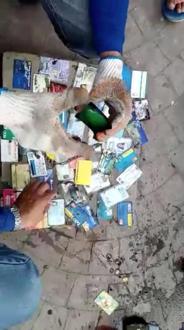 Sanitation workers sort out credit cards and IDs after retrieving wallets from a drain.