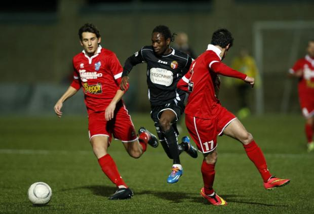 Qormi's Frank Temille (centre) powers his way through Tarxien Rainbows' Triston Caruana (left) and Alexander Cini (right) during their Premier League football match at the Tedesco Stadium in Hamrun on January 27. Photo: Darrin Zammit Lupi
