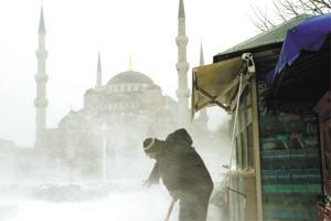 A man shovels snow in front of his kiosk nrear the Blue Mosque (Sultanahmet) during a snow storm in Istanbul yesterday.