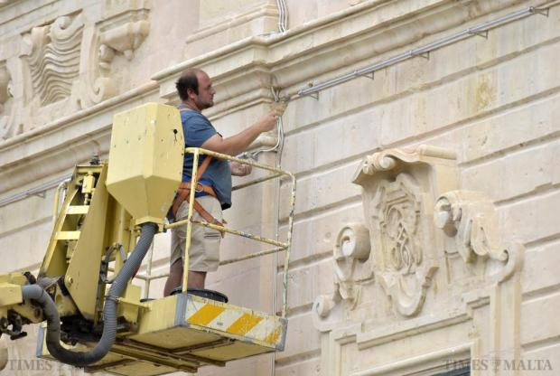 A worker plasters holes created for ducts for the wiring of the new lighting system at Auberge de Castille in Valletta on November 23 Photo: Mark Zammit Cordina.