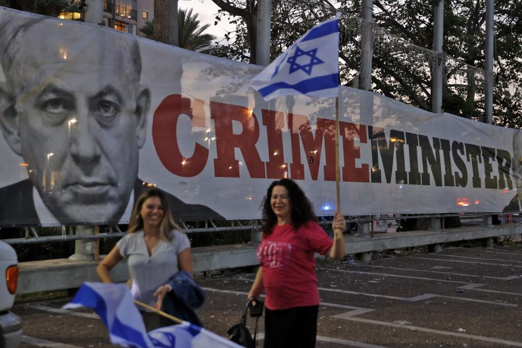 Israeli women carry national flags as they walk past a banner against Prime Minister Benjamin Netanyahu in the central coastal city of Tel Aviv. Photo: AFP
