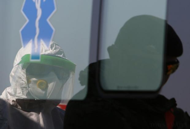 An Armed Forces of Malta soldier in protective clothing is reflected in an ambulance window while taking part in a training exercise at Malta International Airport on April 14. Emergency and medical personnel held an exercise at the airport to test their response should any patient with a highly infectious disease arrive in the country. Photo: Darrin Zammit Lupi