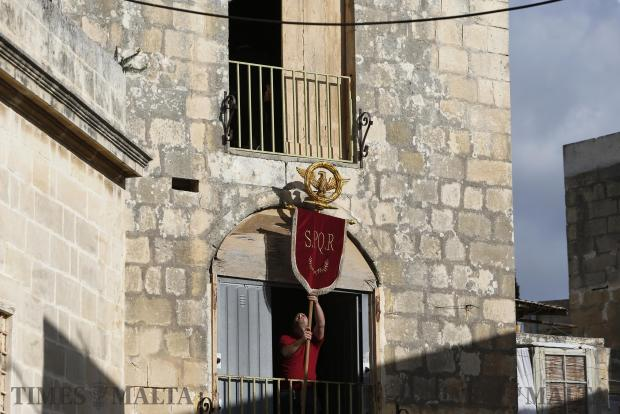 A helper lowers a Roman banner from the balcony of a warehouse being used as a dressing room before a Good Friday procession in Zebbug on March 25. Photo: Darrin Zammit Lupi