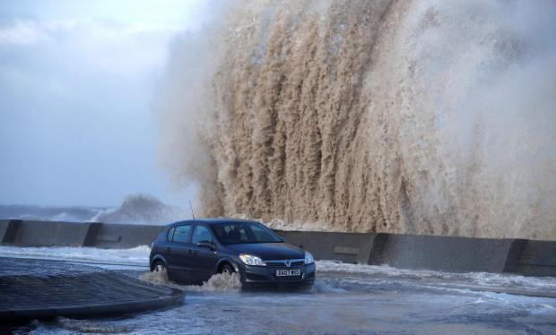 A car drives along a flooded road in New Brighton, on the coast of the Wirral peninsula, in Merseyside.