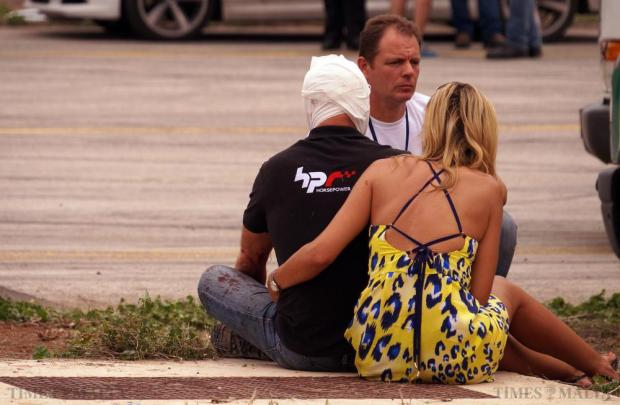 Briton Paul Bailey, his head heavily bandaged, is comforted by his wife after crashing into spectators with his Porsche 918 Spyder supercar during the Papqaqli ghall-Istrina charity event at Malta International Airport on October 4. 28 people were injured, some critically, when the car crashed into bystanders. Photo: Steve Zammit Lupi