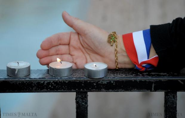 Beatrice le Fraper du Hellen, the French Ambassador to Malta, lights a candle at the Love monument in St Julian's on November 14, during a candlelit vigil for the victims of the terrorist attacks in France. Photo: Matthew Mirabelli