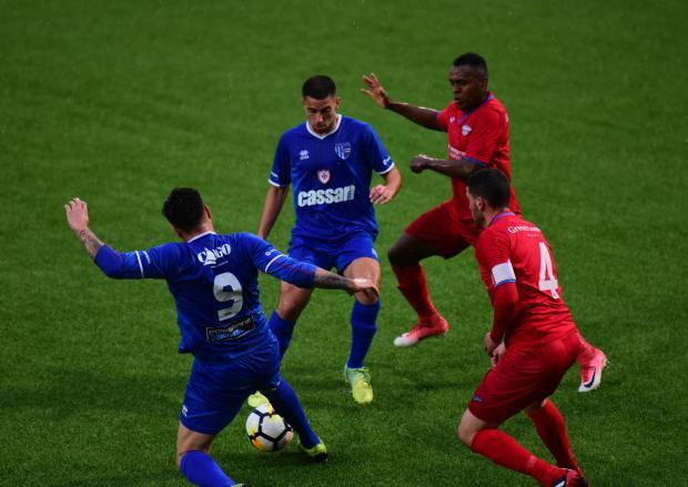 Tarxien Rainbows' Gabriel Aquilina protects the ball from Balzan's players. Photo: Mark Zammit Cordina