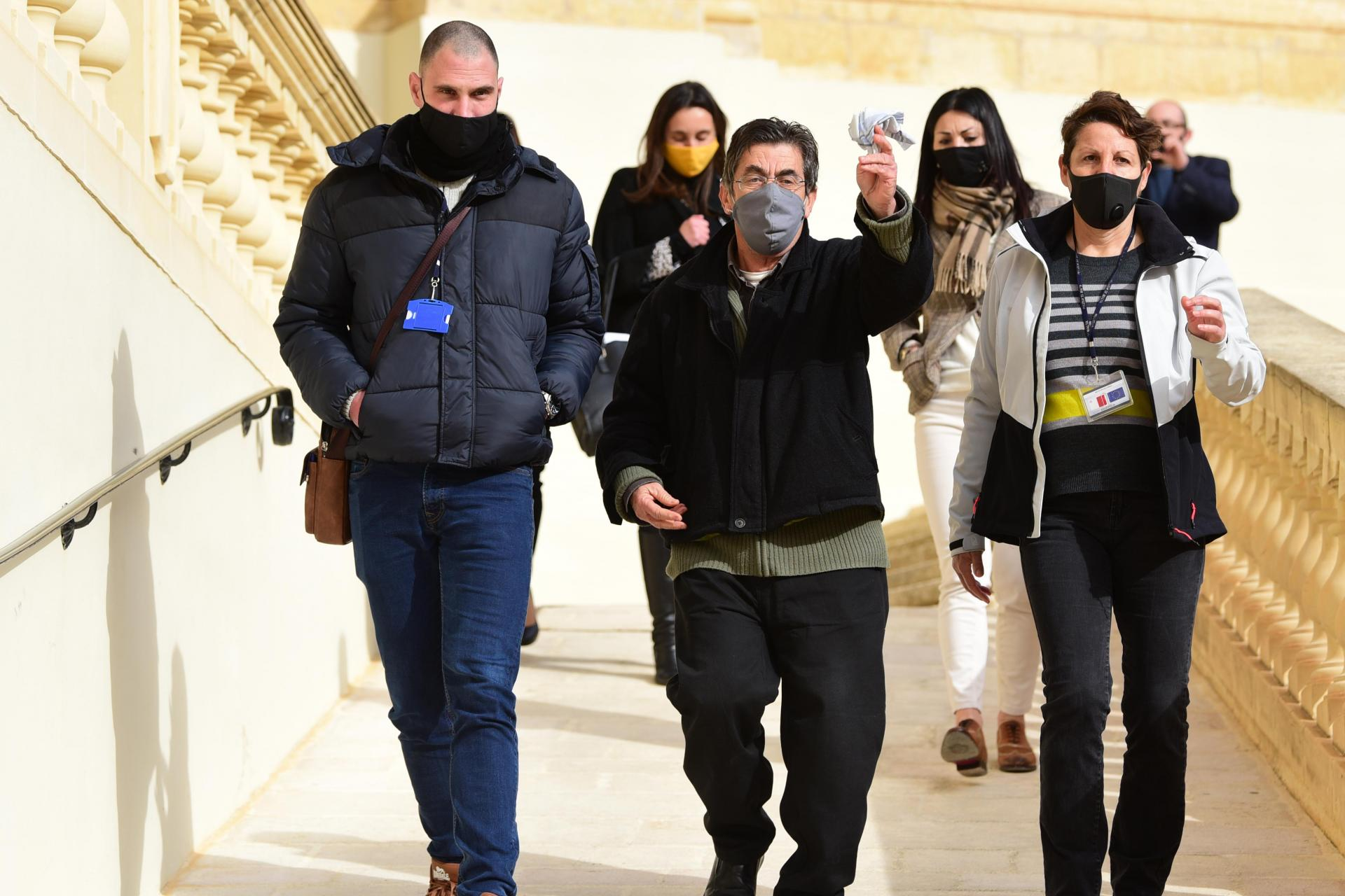 Joseph Cini (centre) waves a handkerchief as he is escorted out of court on January 27. Photo: Mark Zammit Cordina