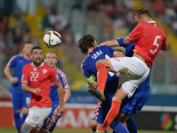 Malta's Andrei Agius (right) and Croatia's Darijo Srna (centre) compete in the air for the ball during their UEFA European Championship Qualifying match at the National Stadium in Ta'Qali on October 13. Photo: Matthew Mirabelli