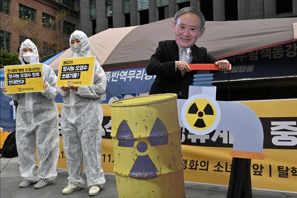 Activistas ambientales surcoreanos vistiendo ropa protectora y una máscara (R) del primer ministro de Japón, Yoshihide Suga, actúan durante una protesta contra la decisión de Japón de liberar las aguas residuales de Fukushima.