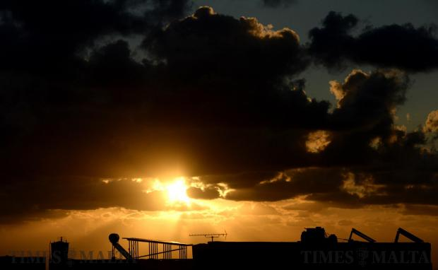 Solar panels are silhouetted by the rising sun in Gharghur on October 26. Photo: Matthew Mirabelli
