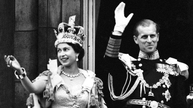 Queen Elizabeth II and the Duke of Edinburgh waving to the onlooking crowds around the gates of Buckingham Palace after the Coronation.