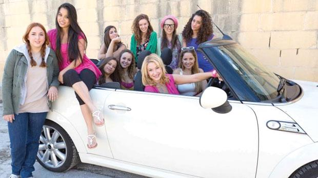 A pretty-in-pink Jo Caruana gets ready for Legally Blonde together with some of the cast.