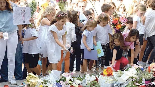 Children placing flowers and cards at a makeshift memorial to slain journalist Daphne Caruana Galizia. Photo: Matthew Mirabelli