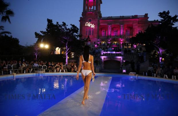 A model walks across a submerged catwalk as she presents a Boux Avenue creation during the sixth edition of the Pink Fashion Show at Villa Rosa in St Julian's on May 26. Photo: Darrin Zammit Lupi