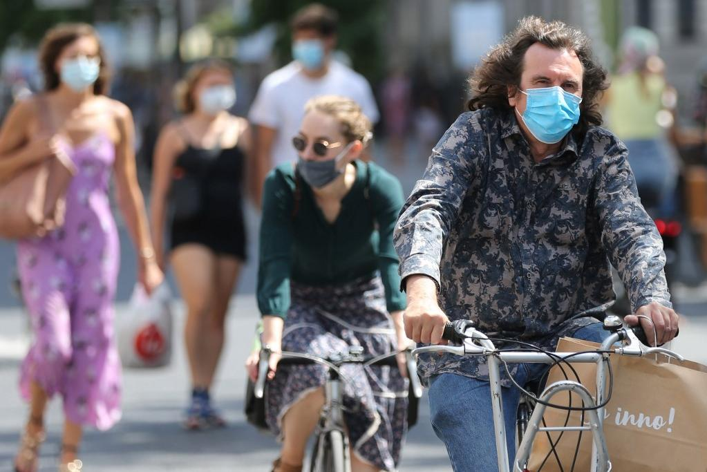 Cyclists wear face coverings in Antwerp as Belgium introduces more stringent coronavirus prevention measures. Photo: AFP