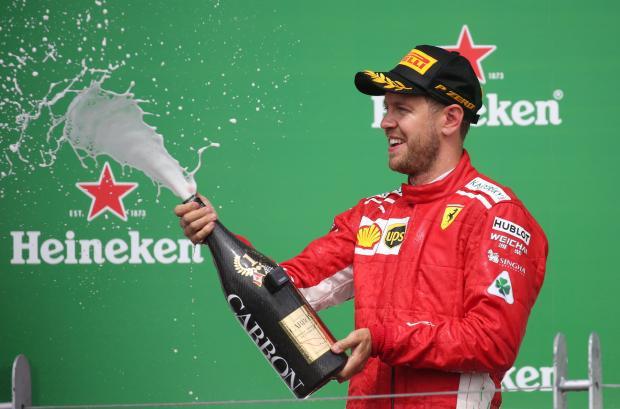 Ferrari's Sebastian Vettel celebrates winning the race on the podium.
