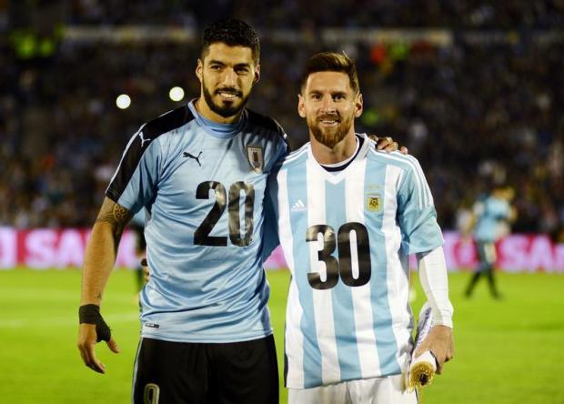 Argentina's Lionel Messi and Uruguay's Luis Suarez pose wearing jerseys to promote their countries joint bid to host the 2030 World Cup finals.