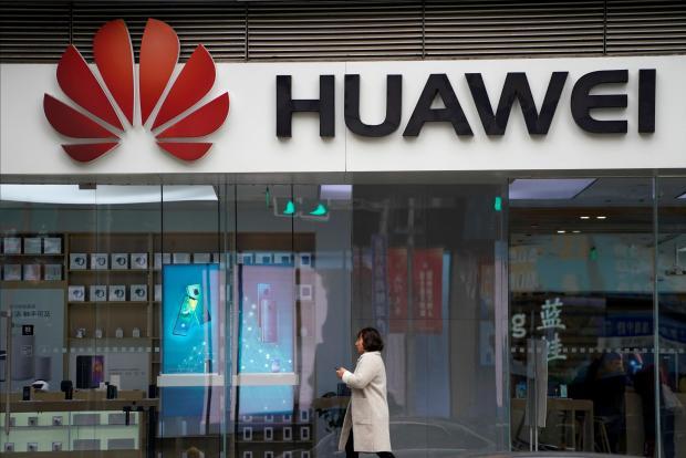 A woman walks by a Huawei logo at a shopping mall in Shanghai.