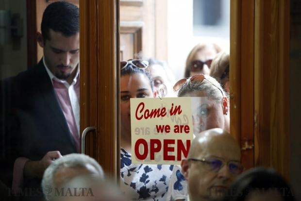 Labour Party supporters stand outside the door of the party's club in Mellieha while listening to Prime Minister Joseph Muscat's address on June 12. Photo: Darrin Zammit Lupi