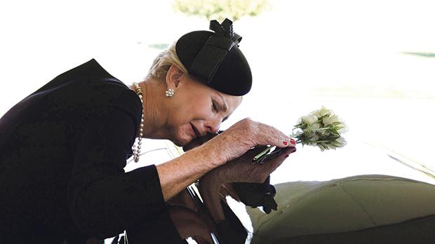 Cindy McCain lays her head on the casket of John McCain, during a burial service at the cemetery at the United States Naval Academy in Annapolis. Photo: Reuters