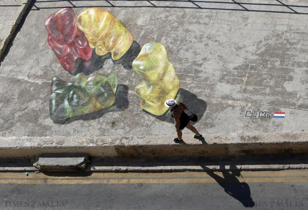 A woman walks past 3D street art of gummy bears by artist Leon Keer of the Netherlands during the Malta Street Art Festival in Valletta's Marsamxett Harbour on July 26. Photo: Darrin Zammit Lupi