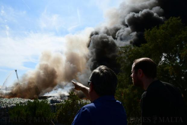 Two persons watch the Sant Antnin recycling plant in Marsascala go up in flames on May 22. Photo: Jonathan Borg