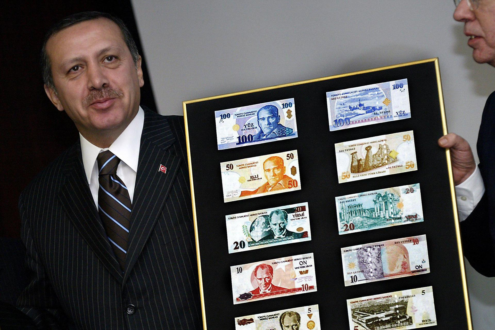 Mr Erdogan poses with new Turkish lira banknotes back in 2004. Photo: AFP
